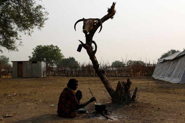 A woman cooks a meal in the town of Pibor, Boma state, east of South Sudan, February 2, 2017. (Photo by Siegfried Modola/Reuters)
