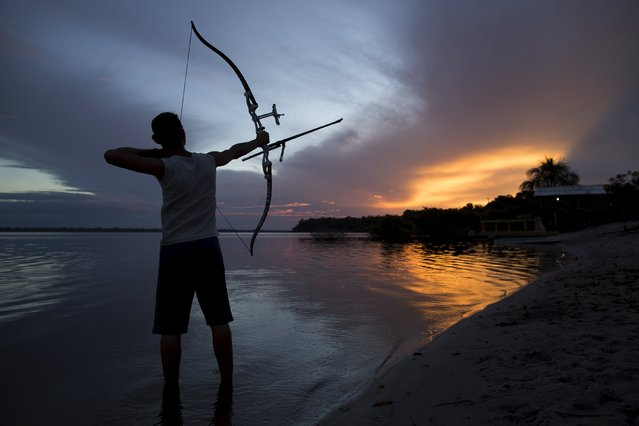 Kambeba Indian, Dream Braga, 18, poses for a picture during sunset on the banks of the Negro river at the village Tres Unidos, Amazon state, May 9, 2015. (Photo by Bruno Kelly/Reuters)