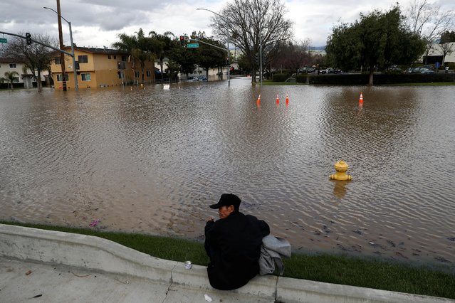 A man sits by the flooded Senter Road after heavy rains overflowed nearby Coyote Creek in San Jose, California, U.S., February 21, 2017. (Photo by Stephen Lam/Reuters)