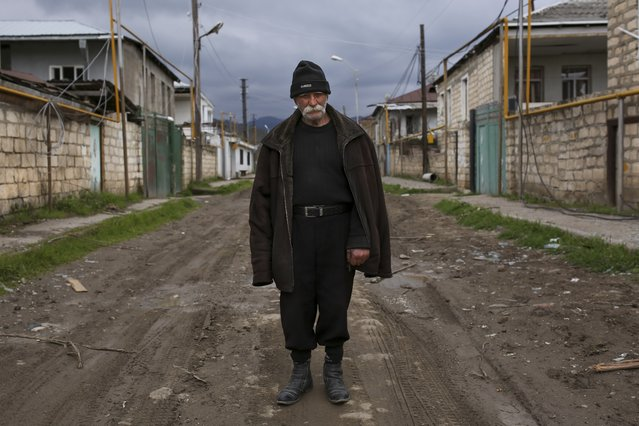 Vagho Beglaryan, 92, an elderly ethnic Armenian man stands in the center of an empty street between abandoned and destroyed houses during the fighting in Martakert province in the separatist region of Nagorno-Karabakh, Azerbaijan, Monday, April 4, 2016. (Photo by Vahan Stepanyan/PAN Photo via AP Photo)