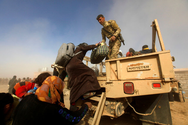 Iraqi soldiers help displaced Iraqis flee their homes as Iraqi forces battle with Islamic State militants, in western Mosul, Iraq February 26, 2017. (Photo by Alaa Al-Marjani/Reuters)