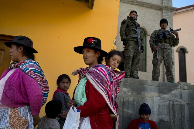 Villagers watch a welcome ceremony for visiting military as soldiers stand guard in Surcubamba, Peru, Thursday, May 21, 2015. The Joint Command of the Peruvian Armed Forces organized a humanitarian mission to Surcubamba, where health care was provided to families from nearby villages in this region called VRAEM, the acronym for Valley of the Apurimac, Ene and Mantaro rivers, where sixty percent of Peru's cocaine originates. (Photo by Rodrigo Abd/AP Photo)