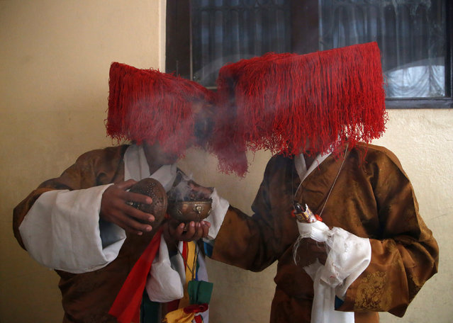 """Tibetan men in traditional attire burn incense during a function organised to mark """"Losar"""", or the Tibetan New Year, in Kathmandu, Nepal March 1, 2017. (Photo by Navesh Chitrakar/Reuters)"""