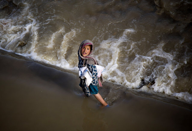 An Afghan girl takes a short cut through a streaming river on the outskirts of Kabul, Afghanistan, Wednesday, May 15, 2013. (Photo by Anja Niedringhaus/AP Photo)