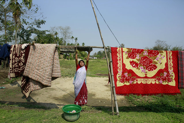 An Indian village woman dries clothes near her house at Panbari village the Duke and Duchess of Cambridge are expected to visit near Kaziranga National Park, east of Gauhati, northeastern Assam state, India, April 12, 2016. The British royal couple is visiting the wildlife park specifically to focus global attention on conservation. The 480-square-kilometer (185-square-mile) grassland park is home to the world's largest population of rare, one-horned rhinos as well as other endangered species, including swamp deer and the Hoolock gibbon. (Photo by Anupam Nath/AP Photo)