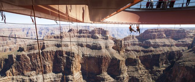 Technicians from Abseilon USA working to clean more than 40 panes of glass underneath the horseshoe-shaped bridge at the Grand Canyon Skywalk in Arizona in this handout picture courtesy of George & Pat Walsh of GPWalshPhotography.com,  taken March 24, 2014. REUTERS/George & Pat Walsh of GPWalshPhotography.com