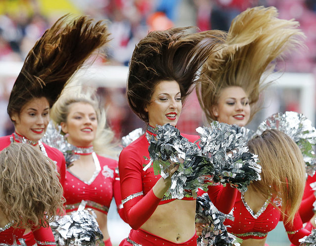 Cheerleaders let their hair fly as they perform prior to a German first division Bundesliga soccer match between 1. FC Cologne and Bayern Munich in Cologne, Germany, March 4, 2017. (Photo by Michael Probst/AP Photo)