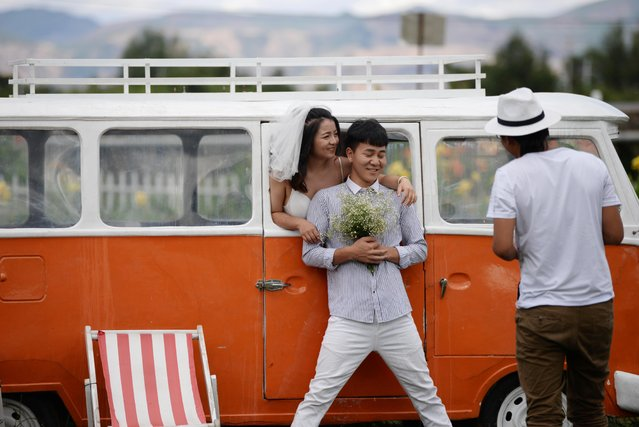 A couple poses with a bus which serves as a prop during their wedding photoshoot near Erhai in Dali Bai Autonomous Prefecture, Yunnan province, China on June 15, 2019. (Photo by Tingshu Wang/Reuters)