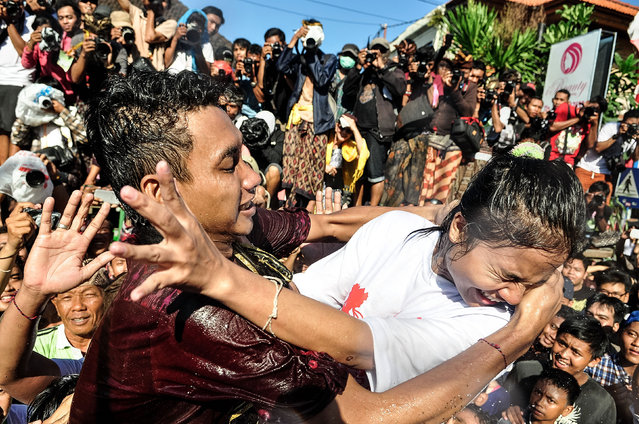 """A young Balinese man tries to kiss a woman during the Kissing Festival known as """"Omed-Omedan"""" at Sesetan village on April 1, 2014 in Denpasar, Bali, Indonesia. (Photo by Agung Parameswara/Getty Images)"""