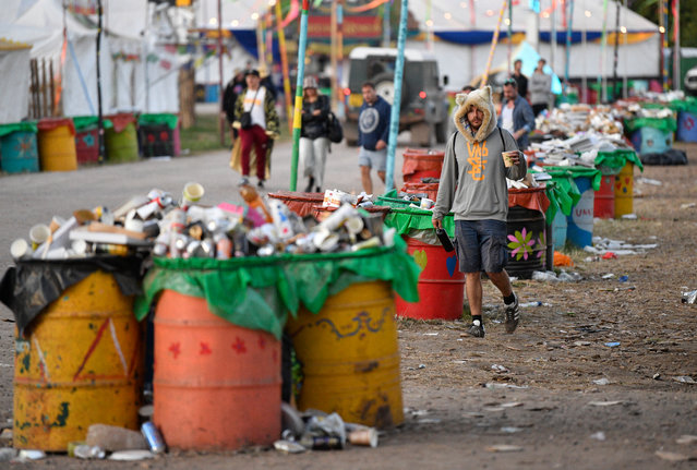 Festival-goers walk amongst the previous nights rubbish at Glastonbury Festival in Pilton, Britain, early 01 July 2019. The Glastonbury Festival of Contemporary Performing Arts is a five-day festival of contemporary performing arts that takes place in Pilton, Somerset, from 26 to 30 June. (Photo by Neil Hall/EPA/EFE)