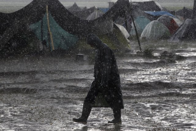 A refugee walks under heavy rainfall at a makeshift camp for migrants and refugees at the Greek-Macedonian border near the village of Idomeni, Greece, April 24, 2016. (Photo by Alexandros Avramidis/Reuters)