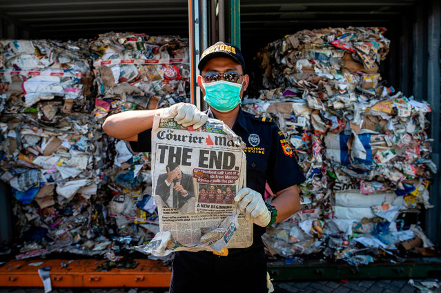 An Indonesian customs officer holds up a newspaper from a container filled with trash originating from Australia, which should have contained only waste paper, but authorities also found hazardous material and household trash, at a port in Surabaya on July 9, 2019. Indonesia said July 9 it would send more than 210 tonnes of garbage back to Australia, as Southeast Asian nations push back against serving as dumping grounds for foreign trash. (Photo by Juni Kriswanto/AFP Photo)