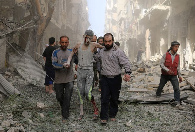Syrians help a wounded youth following an air strike on the Fardous rebel held neighbourhood of the northern Syrian city of Aleppo on April 26, 2016. (Photo by Ameer Alhalbi/AFP Photo)