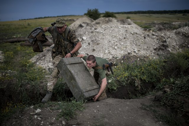 In this photo taken Tuesday, June 23, 2015 Ukrainian servicemen from the Kiev-2 volunteer battalion carry a box of ammunition at the frontline in the village of Krymske, east Ukraine. (Photo by Evgeniy Maloletka/AP Photo)