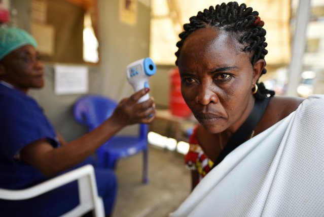 A health worker checks the temperature of a woman as part of the ebola screening upon entering the General Hospital in Goma, Democratic Republic of Congo, July 15, 2019. (Photo by Olivia Acland/Reuters)