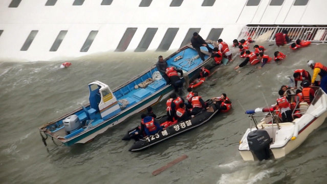 Passengers from the ferry sinking off South Korea's southern coast are rescued by the South Korean Coast guard in the water off the southern coast near Jindo, south of Seoul. (Photo by AP Photo)