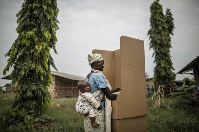 A Burundian woman votes in a polling station in the Kinama neighborhood in Bujumbura, on June 29, 2015. Voting in Burundi's controversial elections opened Monday despite a string of grenade attacks on polling stations, the latest in weeks of violence sparked by the president's defiant bid for a third term. (Photo by Marco Longari/AFP Photo)