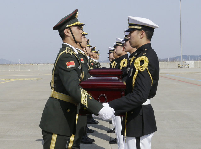 Chinese honor guards, left, receive caskets containing the remains of Chinese soldiers from South Korean honor guards during the handing over ceremony at the Incheon International Airport in Incheon, South Korea, Wednesday, March 22, 2017. The remains of 28 Chinese soldiers killed during the 1950-53 Korean War were transferred from the temporary columbarium in South Korea to the airport to return home for permanent burial. (Photo by Ahn Young-joon/AP Photo)