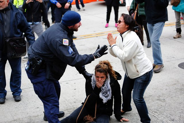 Police rescue a protester during clashes between demonstrators against the American Israel Public Affairs Committee and its supporters in Washington, DC, on March 26, 2017. (Photo by Andrew Biraj/AFP Photo)
