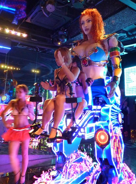 Girls operate a 3.6-meter-tall robot, the main feature of a show at the Robot Restaurant, an adult-oriented cabaret in Tokyo's Kabukicho night entertainment district, on September 12, 2012. (Photo by Kyodo News via Getty Images)