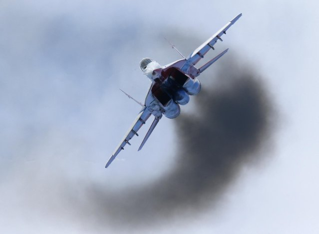 A MiG-29 of the Strizhi (Swifts) performs during an air show at the International Maritime Defence show in St.Petersburg, Russia, Sunday, July 5, 2015. (Photo by Dmitry Lovetsky/AP Photo)