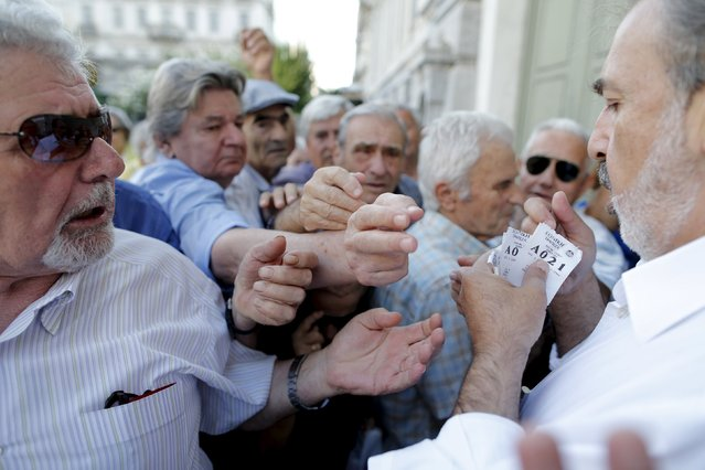 Pensioners are given priority tickets as they wait to receive part of their pensions at a National Bank branch in Athens, Greece, July 6, 2015. Greeks overwhelmingly rejected conditions of a rescue package from creditors on Sunday, throwing the future of the country's euro zone membership into further doubt and deepening a standoff with lenders. (Photo by Christian Hartmann/Reuters)