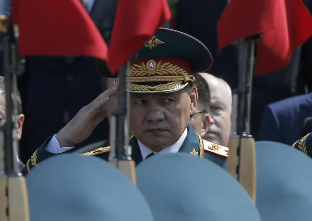 Russian Defence Minister Sergei Shoigu watches honor guards passing by during a wreath-laying ceremony to mark the 71st anniversary of the victory over Nazi Germany in World War Two, at the Tomb of the Unknown Soldier by the Kremlin walls in Moscow, Russia, May 9, 2016. (Photo by Maxim Shemetov/Reuters)