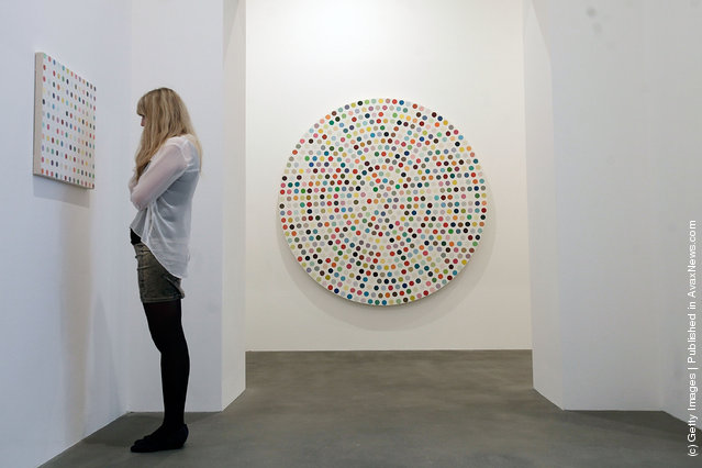 An employee looks at the artwork Hydroquinone, 2006, part of the artist Damien Hirst's exhibition The Complete Spot Paintings