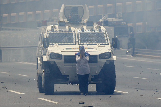 A demonstrator stands in front of a Bolivarian National Guard armored vehicle blocking its way during anti-government protests in Caracas, Venezuela, Wednesday, April 19, 2017. (Photo by Ariana Cubillos/AP Photo)