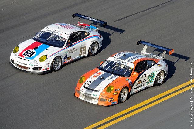 The #59 GT Brumos Racing Porsche GT3 driven by Leh Keen, Andrew Davis, Hurley Haywood and Marc Lieb race with the #12GT Porsche GT3 driven by Scott Rettich, Jon Miller, Hal Prewitt, Matt Schneider and Darryl Shoff during the Rolex 24