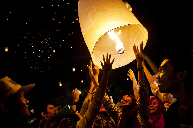 "Indonesian Muslim woman with Buddhist followers releases a lantern into the air on Borobudur temple during Vesak Day, commonly known as ""Buddha's birthday"", at the Borobudur Mahayana Buddhist monument on May 6, 2012 in Magelang, Indonesia. (Photo by Ulet Ifansasti/Getty Images)"