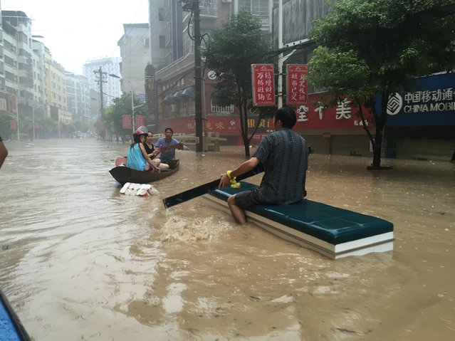 Residents boat in flood waters caused by a rainstorm on July 15, 2015 in Songtao Miao Autonomous County, Tongren City, Guizhou Province of China. One person has died after being struck by lightning and about 135,000 people have been affected by a rainstorm which hit Songtao Miao Autonomous County on Tuesday night to Wednesday morning. (Photo by ChinaFotoPress/ChinaFotoPress via Getty Images)