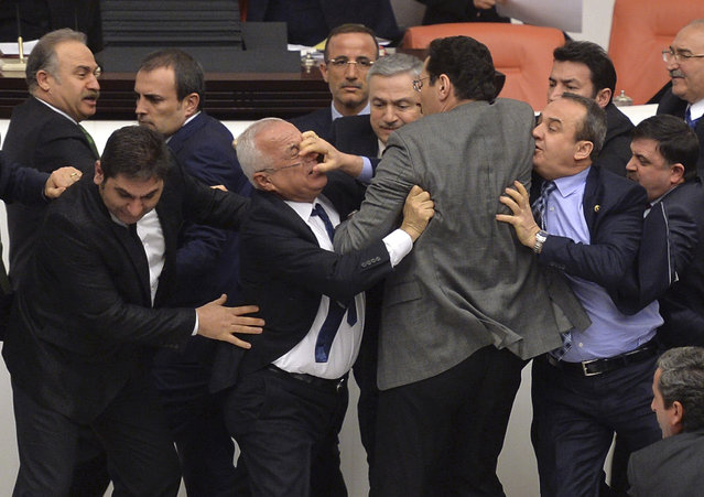 Lawmakers from the main opposition Republican People's Party (CHP) and ruling AK Party (R) scuffle during a debate on a legislation to boost police powers, at the Turkish Parliament in Ankara, Turkey, February 19, 2015. (Photo by Reuters/Stringer)