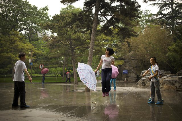 In this Sunday, May 17, 2015 photo, a girl holds an umbrella as she skips rope during a rain shower at a park in Beijing. (Photo by Mark Schiefelbein/AP Photo)