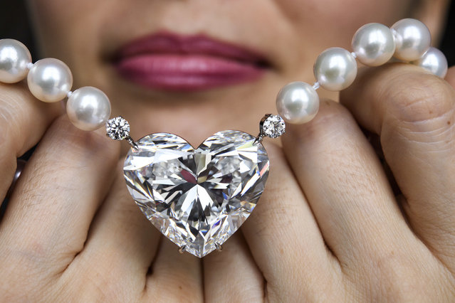"A Christie's employee displays The flawless heart-shaped Boehmer and Bassenge ""La legende"" diamond during a preview at the Christie's, in Geneva, Switzerland, Thursday, May 11, 2017. It is estimated to sell between 14-20 millions US dollars. The auction will take place in Geneva, on May 17. (Photo by Martial Trezzini/Keystone via AP Photo)"