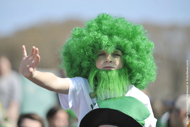 Max Long, 7, sports a green afro and beard as he watches the St. Patrick's Day parade from his father's shoulders on March 17, 2012 in Chicago
