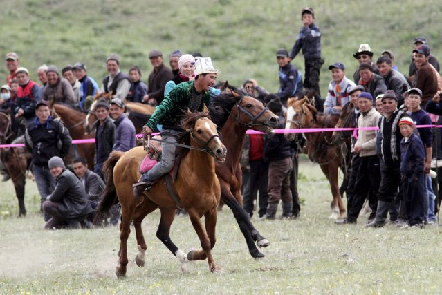 "A man and a woman take part in the ""Kyz Kuumai"", or girl-chasing, competition during the Kyrgyz national horse games and festival near the Tulpar-Kul lake in the Chon Alai mountain range, some 3500 metres (11483 feet) above sea level, in the Osh region of Kyrgyzstan, July 25, 2015. (Photo by Vladimir Pirogov/Reuters)"