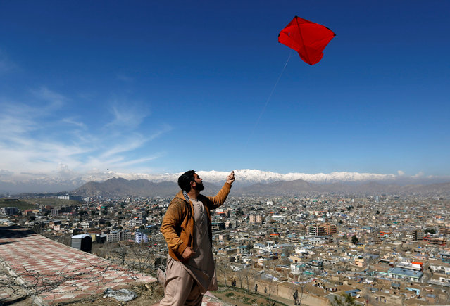 An Afghan man flies a kite on a hilltop during Afghan spring and new year celebrations in Kabul, Afghanistan March 23, 2017. (Photo by Mohammad Ismail/Reuters)