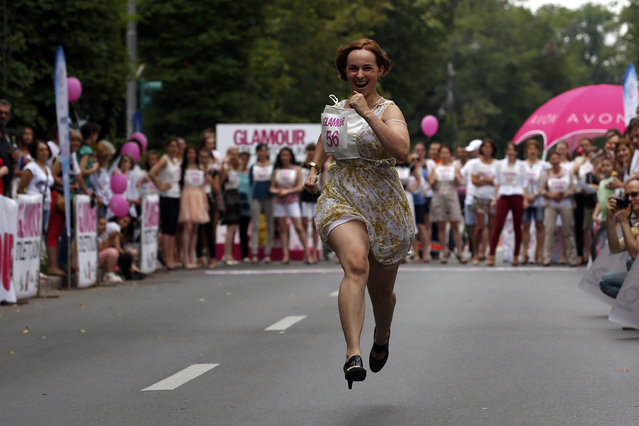 A participant runs in high-heels as she competes in the Stiletto Run in Bucharest June 14, 2014. The annual 50 metres race requires participants to wear high-heels that are at least 7cm tall. (Photo by Bogdan Cristel/Reuters)