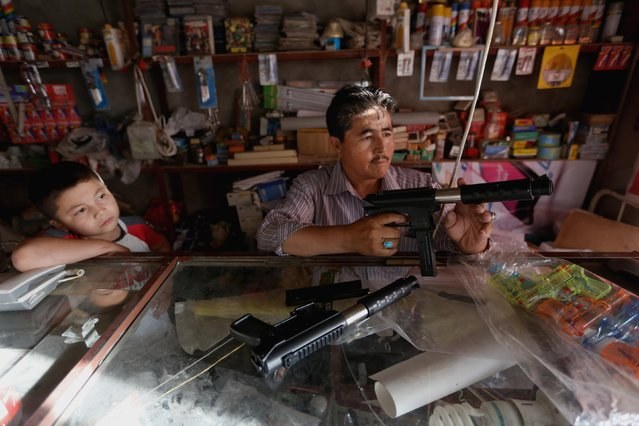 In this Saturday, July 25, 2015 photo, Murad Ali Gharibyar 45, an Afghan toy guns salesman holds a toy at his shop, in Kabul, Afghanistan. (Photo by Rahmat Gul/AP Photo)