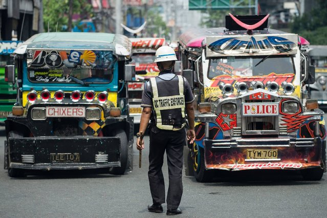 "Jeepneys are seen as an enforcer manages traffic at a busy street in Manila on May 30, 2017. Jeepneys, once hailed as the ""King of the Road"" and a cultural symbol in the Phillipines to rival New York's yellow taxis, may soon disappear from Manila's gridlocked streets, as authorities move to phase out the Philippines' iconic World War II-era minibuses, citing pollution and safety concerns. (Photo by Noel Celis/AFP Photo)"