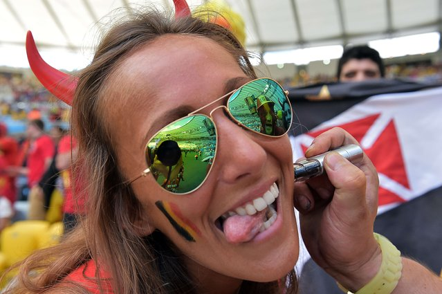 Belgian supporter has her face painted in national colours as she cheers for her team ahead of the Group H football match between Belgium and Russia at The Maracana Stadium in Rio de Janeiro on June 22, 2014, during the 2014 FIFA World Cup. (Photo by Gabriel Bouys/AFP Photo)