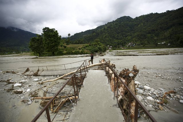 A man stands on a damaged trail bridge that was washed away after the river flooded due to heavy rainfall in Kaski District July 31, 2015. (Photo by Navesh Chitrakar/Reuters)