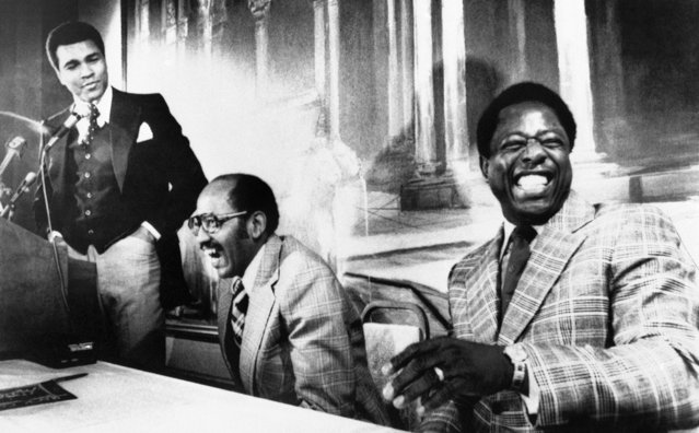 """Retired baseball player Henry Aaron, right, rocks in laughter as he hears former boxer Muhammad Ali, left, describe the wonder to those in the presence of the """"world's greatest boxer and the greatest baseball player of all time"""" at an Atlanta press conference on December 1, 1976. Ali reaffirmed his retirement from boxing, promoted his biographical movie and the business venture of Leroy Johnson, center, Atlanta businessman who sponsored Ali's 1970 comeback. (Photo by Charles Kelly/AP Photo)"""