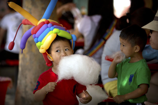 A boy eats cotton candy while wearing a hat made of balloons at a public park in Beijing, Thursday, June 1, 2017. Thursday is International Children's Day, a holiday for children celebrated in many countries around the world. (Photo by Mark Schiefelbein/AP Photo)