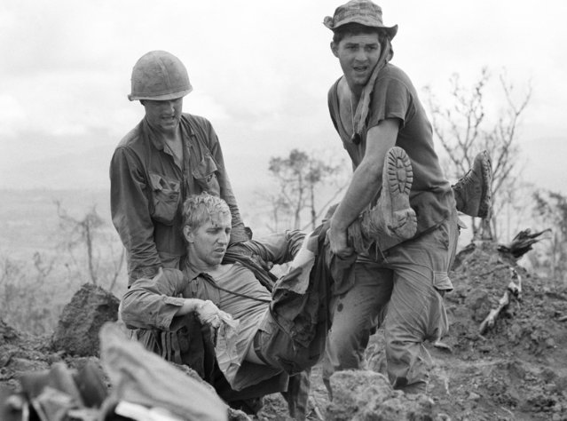 Two troopers of the U.S. 4th Infantry Division carry a wounded soldier out of the line of North Vietnamese fire to a protective bunker on Hill 990 in South Vietnam's Central Highlands, June 2, 1968. The troops were under enemy siege and were unable to evacuate their wounded or dead comrades. (Photo by Rick Merron/AP Photo)
