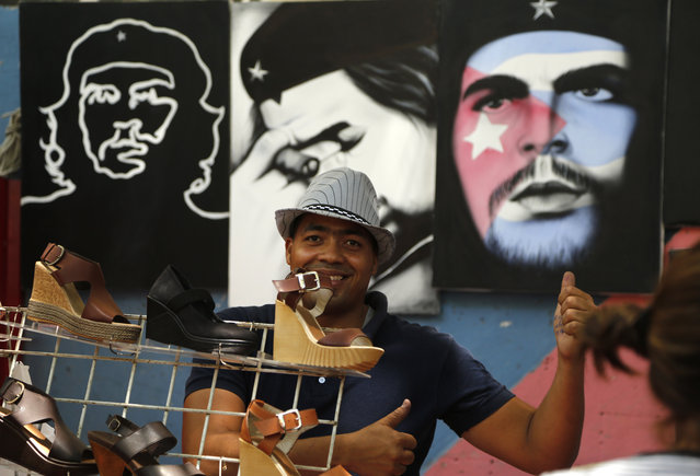 """A vendor gives a thumbs up to the camera as he sells shoes and paintings of Cuba's revolutionary hero Ernesto """"Che"""" Guevara in Havana, Cuba, Tuesday, April 14, 2015. (Photo by Desmond Boylan/AP Photo)"""