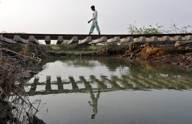 A villager walks on a railway track that was damaged after heavy monsoon rains near Patdi village in Gujarat, August 3, 2015. (Photo by Amit Dave/Reuters)