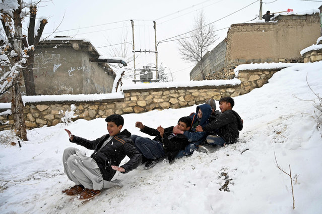 Children play on snow in their neighbourhood in Kabul on January 2, 2020. (Photo by Wakil Kohsar/AFP Photo)