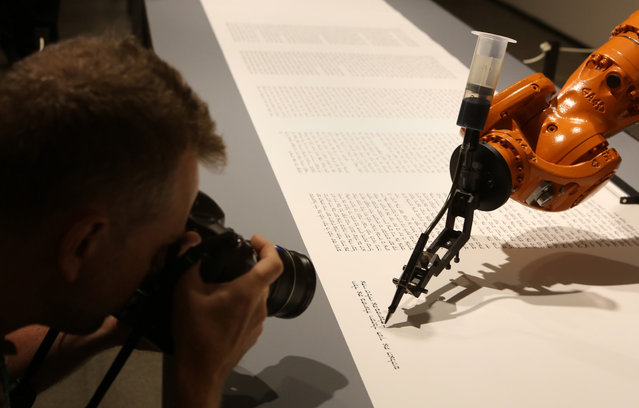 "A photographer takes a picture of an industrial robot, an installation work called ""bios (torah)"" by the artist group robotlab, as it begins writing a Torah in the Jewish Museum in Berlin, Germany, on Jule 10, 2014. At the speed of a human, the robot writes a total of 304,805 Hebrew letters on an 80-meter roll of paper. The finished scroll will not be considered halakhic, or meeting the requirements for use for religious purposes. (Photo by Adam Berry/Getty Images)"